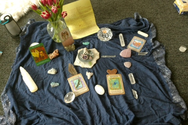oracle cards, crystals, candle, etc. on blanket for space clearing